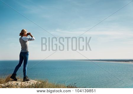 Girl With Binoculars At The Mountains In The Rays Of The Evening Sunset. Young Beautiful Woman On Na