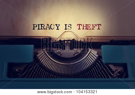 closeup of a blue retro typewriter and the text piracy is theft written with it in a yellowish foil