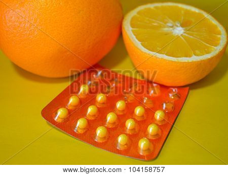 Oranges and vitamin C on yellow background