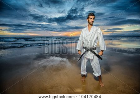 karate black belt master with dramatic sky on the beach poster