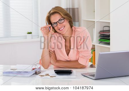 Woman With Invoice And Laptop At Desk