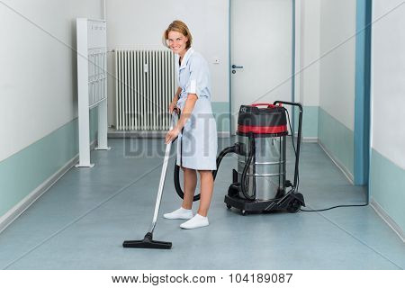 Young Female Cleaner In Uniform Vacuuming Floor poster