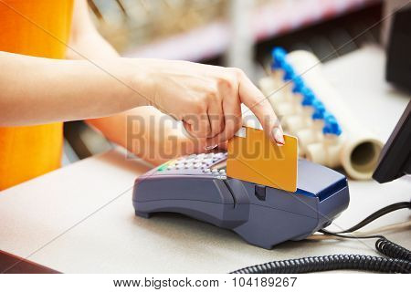 sale assistant cashier accepting credit bank card and using payment terminal for purchase poster