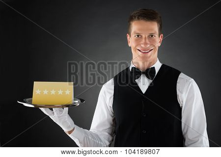 Portrait Of Happy Waiter Holding Plate With Star Rating Board poster