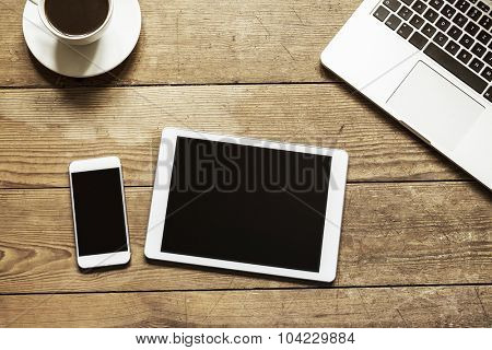 empty phone and tablet on a wooden workspace table