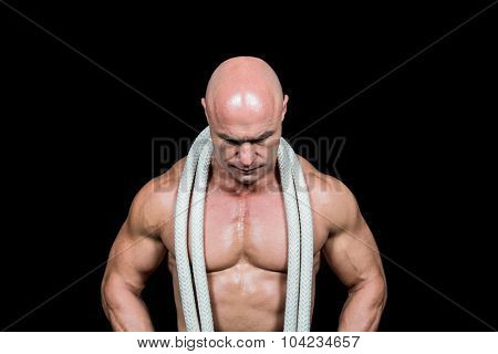Bald man with rope around neck against black background