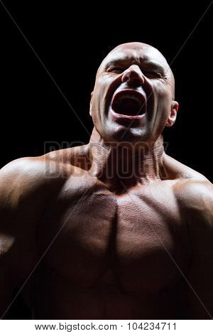 Aggressive muscular man against black background