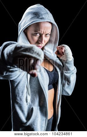 Portrait of female fighter in hood with fighting stance against black background
