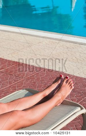 Legs Of Beautiful Young Unrecognizable Girl In A Bikini Lying On A Beach Bed Near The Hotel Swimming