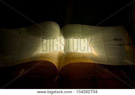 Glowing book of magic spells with open pages poster