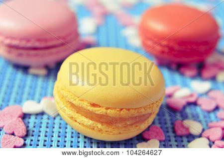 closeup some appetizing macarons with different colors and flavors on a blue tablemat with heart-shaped sprinkles