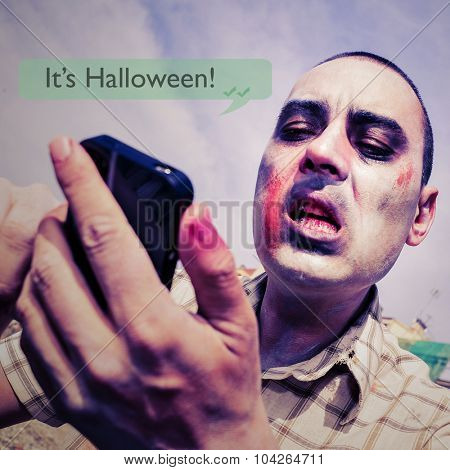 closeup of a scary zombie sending or receiving a text message in his smartphone with the text it is halloween