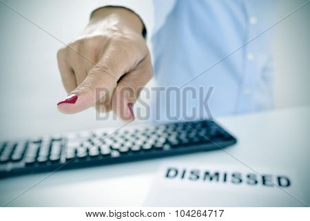 closeup of a businesswoman sitting at her desk, with a document with the text dismissed on it, pointing with her finger the way out