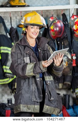Portrait of happy firewoman in uniform holding digital tablet at fire station