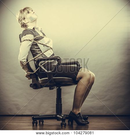 Afraid businesswoman bound by contract terms and conditions with mouth taped shut. Scared woman tied to chair become slave. Business and law concept. Instagram filtered. poster