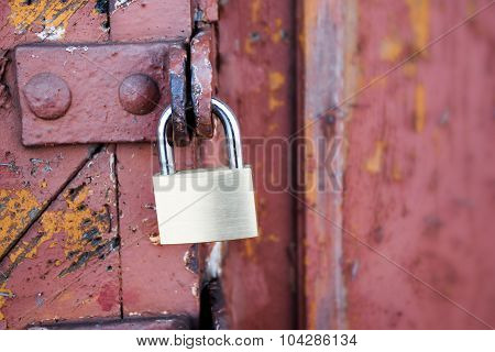 New Padlock On An Old Red Wooden Gate