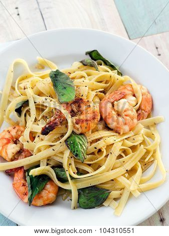 Fettuccini with shrimps and basil leaves