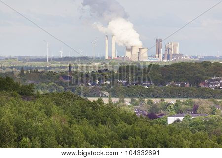Distant Power Station In Rural Landscape Surrounded By Wind Turbines
