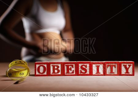 Word 'OBESITY' with measruing tape in front of woman's body holding her big belly poster