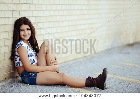 young girl leaning on brick wall