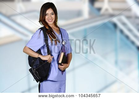 Minority nursing student with her books going to class