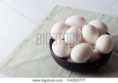 Eggs in a bowl on beige napkin aside