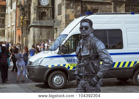 Meme-artist in the form of futuristic police posing on old Town Square