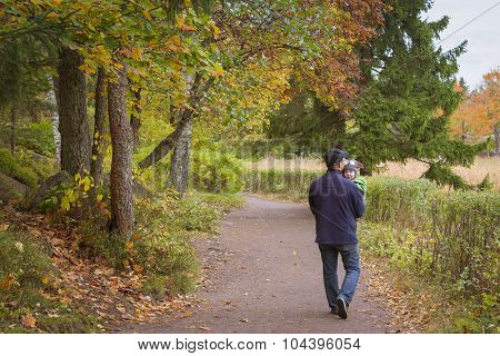 The man with the child walks in the autumn Monrepos park