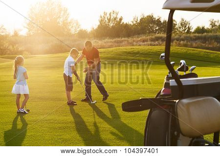 Casual Kids At A Golf Field Holding Golf Clubs Studing With Trainer