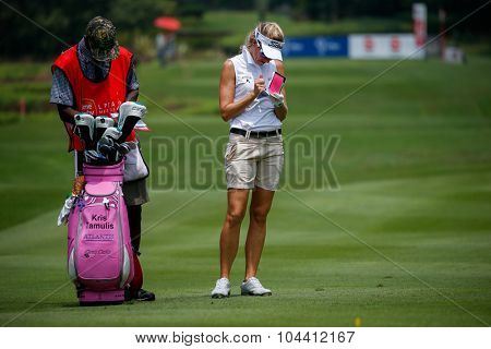 KUALA LUMPUR, MALAYSIA - OCTOBER 09, 2015: USA's Kris Tamulis takes down notes on the sixth hole fairway of the KL Golf & Country Club at the 2015 Sime Darby LPGA Malaysia golf tournament.