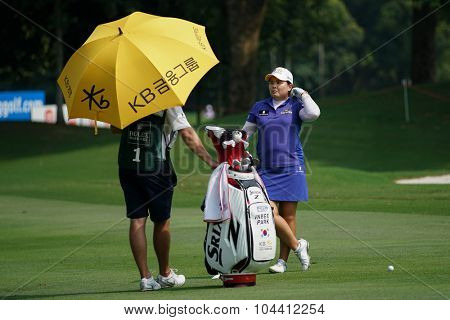 KUALA LUMPUR, MALAYSIA - OCTOBER 09, 2015: South Korea's Inbee Park discusses with her caddy on the fairway of the KL Golf & Country Club at the 2015 Sime Darby LPGA Malaysia golf tournament.