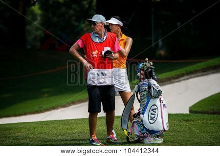 KUALA LUMPUR, MALAYSIA - OCTOBER 09, 2015: USA's Michelle Wie discusses with her caddy from the sixth hole fairway of the KL Golf & Country Club at the 2015 Sime Darby LPGA Malaysia golf tournament.