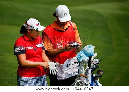 KUALA LUMPUR, MALAYSIA - OCTOBER 09, 2015: South Korea's Ha Na Jang discusses with her caddy at the 6th hole fairway of the KL Golf & Country Club at the 2015 Sime Darby LPGA Malaysia golf tournament.