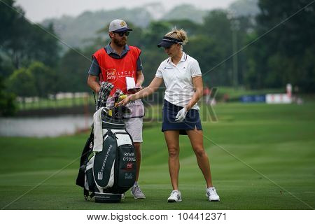 KUALA LUMPUR, MALAYSIA - OCTOBER 09, 2015: USA's Ryan O'Toole checks with her caddy on the sixth hole fairway of the KL Golf & Country Club at the 2015 Sime Darby LPGA Malaysia golf tournament.