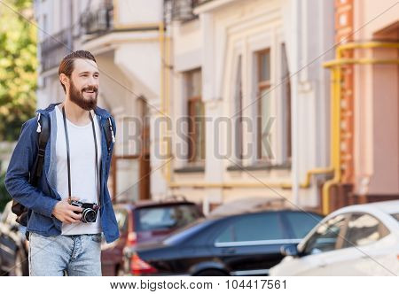 Cheerful young man is traveling across town