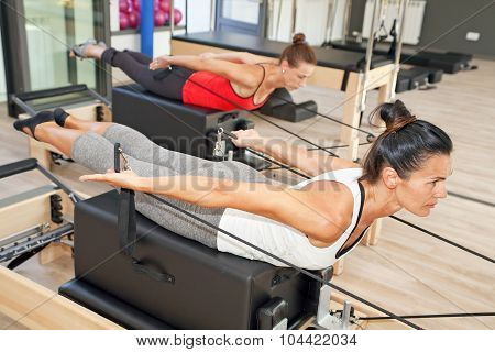 Two girls are exercising pilates using pilates device reformer poster
