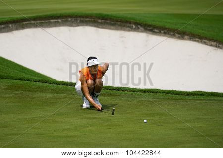 KUALA LUMPUR, MALAYSIA - OCTOBER 09, 2015: USA's Michelle Wie lines her putt at the 18th hole green at the KL Golf & Country Club at the 2015 Sime Darby LPGA Malaysia golf tournament.