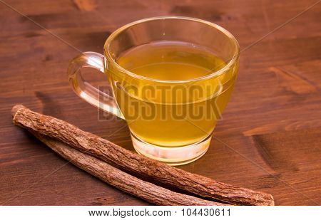Herbal tea licorice inside cup on wood