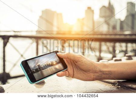Woman Watching Photo Of New York City Skyline On The Smart Phone.