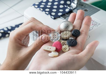 Choose Buttons In Woman Hands , Close Up