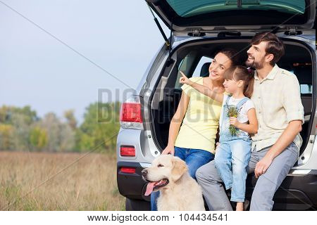 Cute friendly family is resting in forest near vehicle