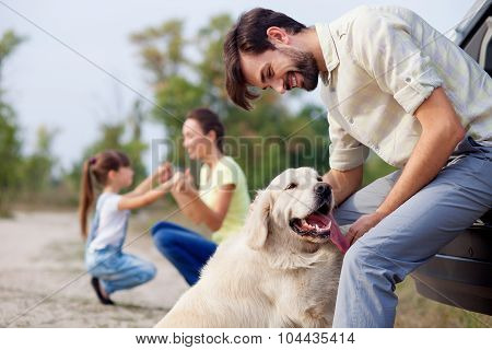 Cute parents and child with pet in the nature