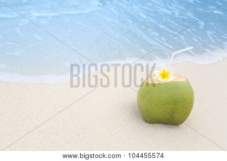 Refreshing tropical drink on a white sand beach with incomming waves poster