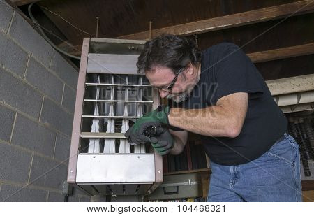 Technician Checking Out A Overhead Gas Furnace