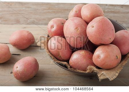 red potatoes in a bowl on wooden background