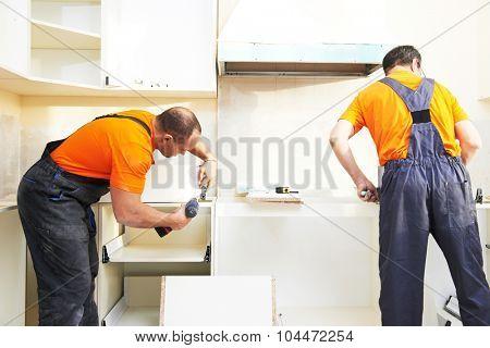 Craftsman kitchen carpenter workers at kitchen furniture set installation service work poster