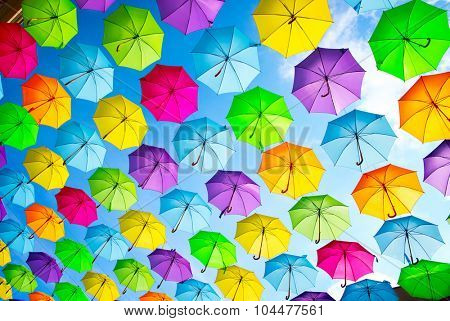 Colorful umbrellas background. Coloruful umbrellas urban street decoration. Hanging Multicoloured umbrellas over blue sky. Abstract color background