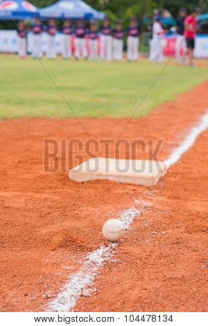 Baseball And Base On Baseball Field With Players And Coach On Background