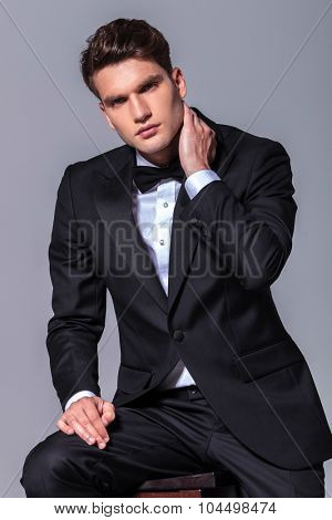 Handsome business man holding one hand to his neck while sitting on a chiar.