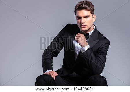Front view of a young handsome business man sitting while holding his right hand on his leg.